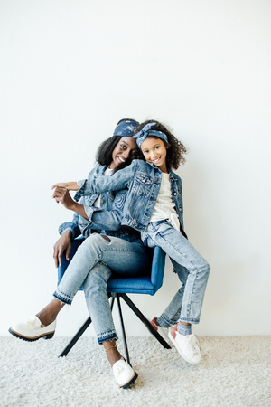Smiling African American daughter near mother in chair at home Reklamní fotografie