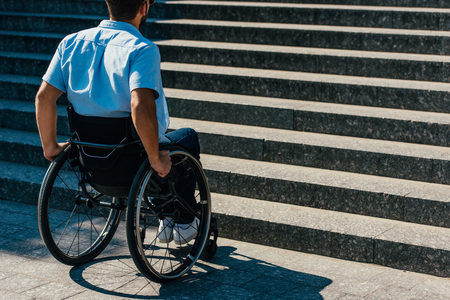 Back view of disabled man using wheelchair on street and stopping near stairs without ramp Archivio Fotografico - 111569352