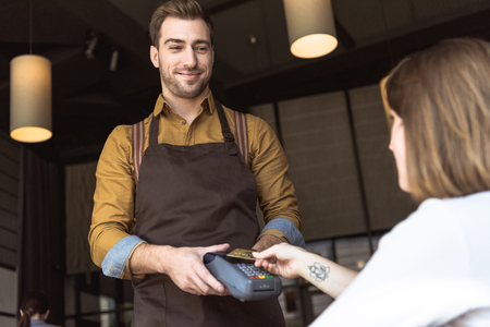 Happy young waiter holding payment terminal while client doing contactless purchase with credit card in cafe