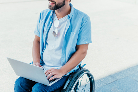 Cropped image of bearded man in wheelchair using laptop on street Stock Photo