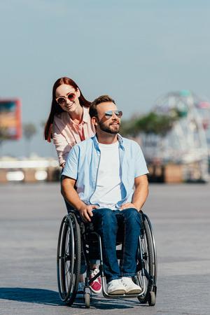 Attractive smiling girlfriend pushing handsome boyfriend in wheelchair on street