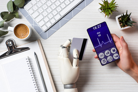 Partial view of businessman with cyborg hand holding credit card and using smartphone with medical application on screen at table with coffee cup in office Stock Photo