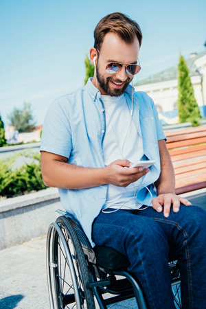 Smiling handsome man in wheelchair using smartphone and listening to music on street Stockfoto