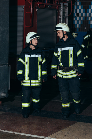 Firefighters in protective uniform and helmets at fire department Stockfoto