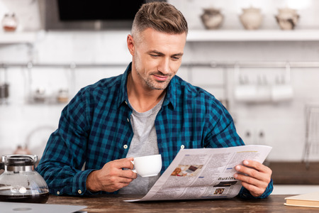 Smiling man in checkered shirt holding cup of coffee and reading newspaper at home 版權商用圖片 - 111569791