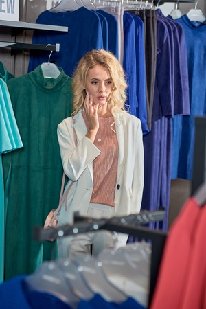 Attractive young woman looking at fashionable clothes while shopping in boutique Foto de archivo - 111569764