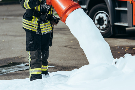 Cropped shot of firefighter extinguishing fire with foam on street
