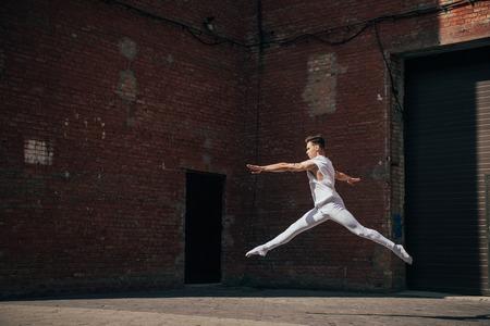 Young ballet dancer in jump on city street Foto de archivo - 111569821