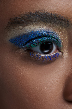 Partial view of African American woman with bright blue eye shadow Stock Photo