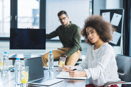 Multicultural businessman and businesswoman looking at camera in office