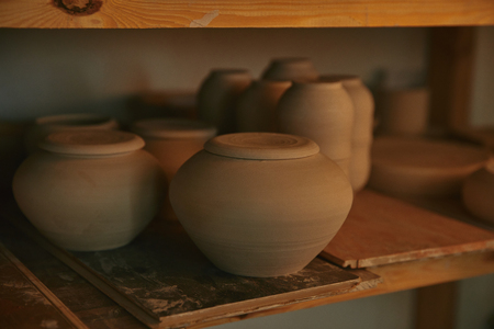 Close up view of ceramic bowls and dishes on wooden shelves at pottery studio