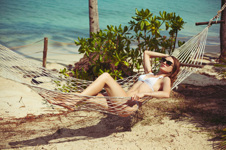 Young woman in bikini lying in hammock on beach Stok Fotoğraf - 111570086