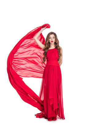 Attractive girl posing in red chiffon dress with veil, isolated on white background