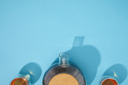 Top view of teapot and cups with fresh tea on blue background
