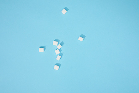 Top view of sweet white tasty sugar cubes with shadows on blue background