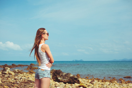 Side view of young woman in sunglasses looking at ocean