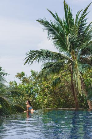 Beautiful girl in bikini leaning on poolside and looking away