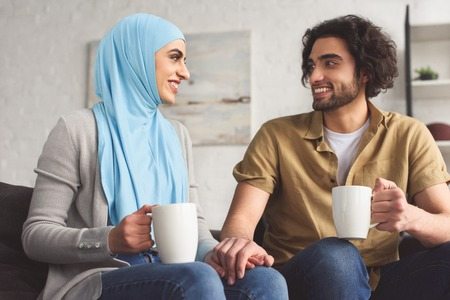 Smiling Muslim couple holding hands and holding cups of coffee at home