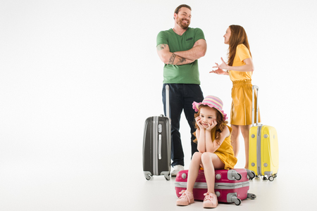 Upset little child sitting on suitcase with parents behind isolated on white background, travel concept