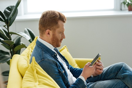 Young man sitting on sofa with smartphone in hands Stok Fotoğraf
