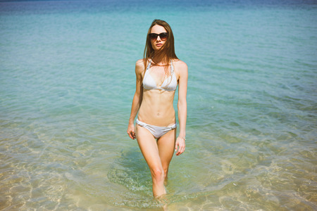 Portrait of young woman in bikini and sunglasses standing in ocean