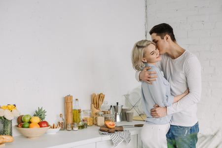 Fidanzato che abbraccia e bacia la fidanzata in cucina