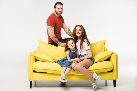 Happy family sitting on couch isolated on white background
