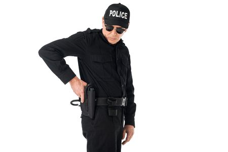 Policeman in uniform pulling out gun isolated on white background