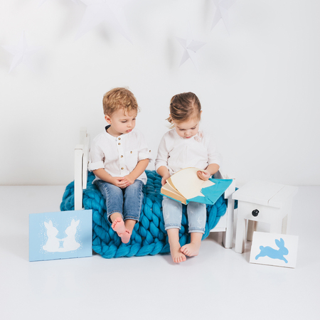Adorable little kids sitting on blue knitted plaid and reading book and rabbit cards, Easter concept Фото со стока - 111571894