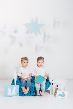 Adorable little kids sitting on blue knitted plaid with book and rabbit cards, Easter concept Фото со стока - 111571903