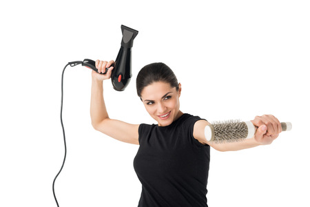 Female hairdresser fooling with dryer and hairbrush isolated on white background 스톡 콘텐츠