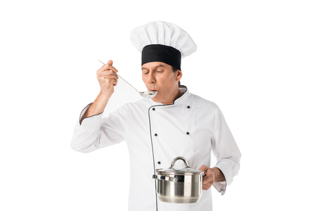 Man in chef uniform holding pan and tasting food isolated on white background
