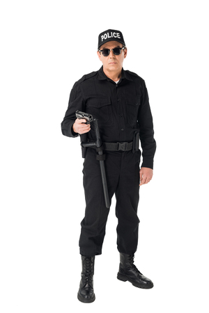 Serious policeman in sunglasses holding gun isolated on white background