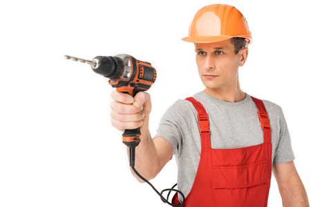 Professional builder in overalls and hardhat holding drill isolated on white background