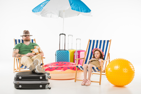 Father and daughter in hats sleeping in sun loungers isolated on white background, travel concept