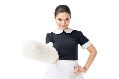 Brunette maid in professional uniform holding duster isolated on white background