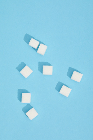 Close-up view of sweet white tasty sugar cubes on blue background