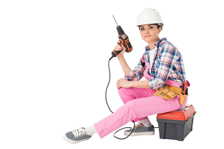 Professional builder in overalls and hardhat holding drill while sitting on toolbox isolated on white background