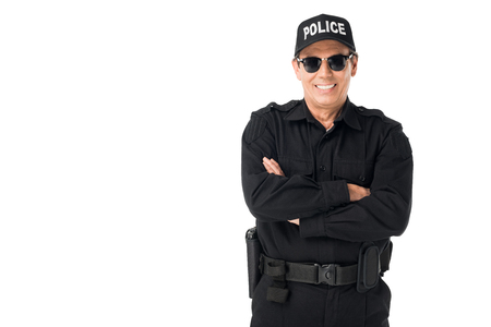 Smiling policeman wearing uniform with arms folded isolated on white background