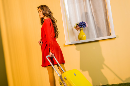 Beautiful retro styled woman in red dress walking with travel bag at home