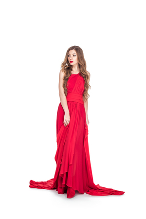 Beautiful glamorous woman posing in red dress, isolated on white background Stock Photo