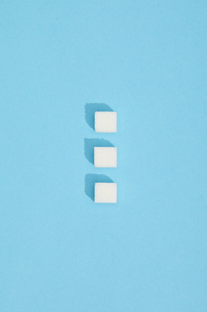 Sweet white sugar cubes with shadows on blue background
