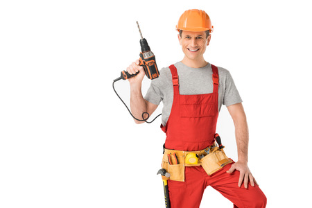 Handsome builder in uniform with tool belt holding drill isolated on white background
