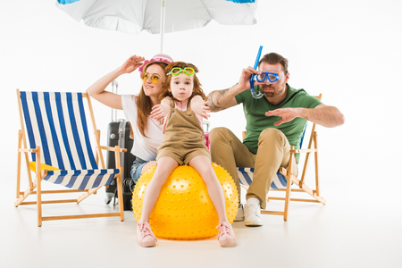 Family in swimming goggles depicting swim with sunshade, sun loungers and ball isolated on white background, travel concept