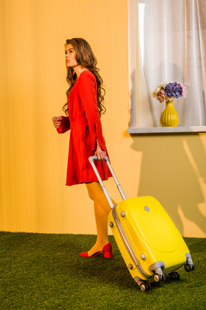 Side view of beautiful retro styled woman in red dress standing with wheeled bag at home, travel concept
