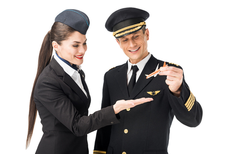 Airline captain and stewardess holding toy plane isolated on white background Фото со стока