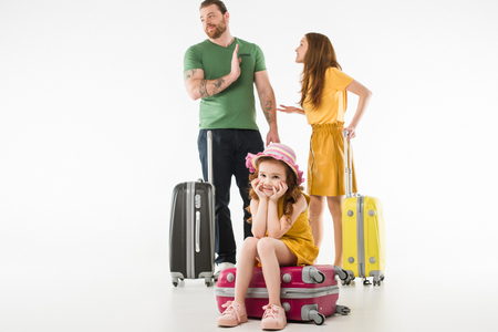 Upset little child sitting on suitcase while parents arguing isolated on white background, travel concept
