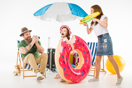 Father taking shot on camera while mother aiming water gun on daughter with flotation ring isolated on white background Stock Photo