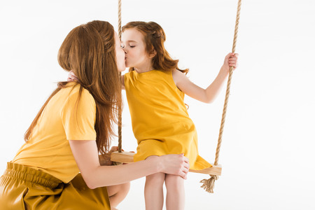 Daughter sitting on swing and kissing mother isolated on white background Reklamní fotografie