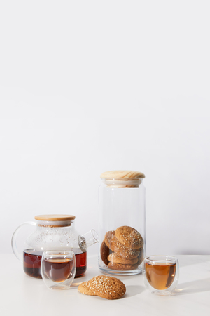 Close-up view of tea in cups, delicious cookies and teapot on grey background